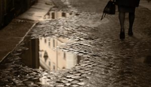 Lower view of professional woman walking on a rainy cobblestone road