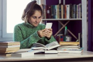 Woman sitting at desk, procrastinating with a smartphone next to open textbooks
