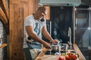Man talking on the phone while cooking on a stove and holding a soccer ball