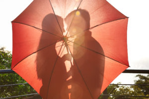 Silhouette of an affectionate couple standing behind an umbrella