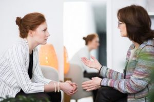Woman sitting next to mirror that reflects her while speaking with a therapist
