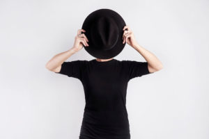 Woman holding up a black hat to hide her face