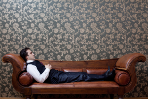 Man in suit lies on leather couch.
