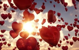 Red heart balloons floating in sky with sun in background.