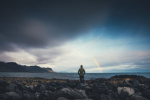 Person watching a rainbow in a cloudy sky