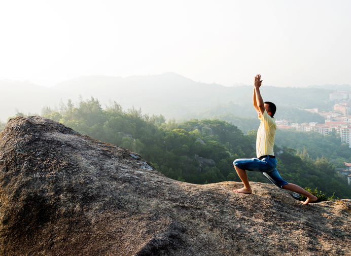Man in yoga pose on rock ledge