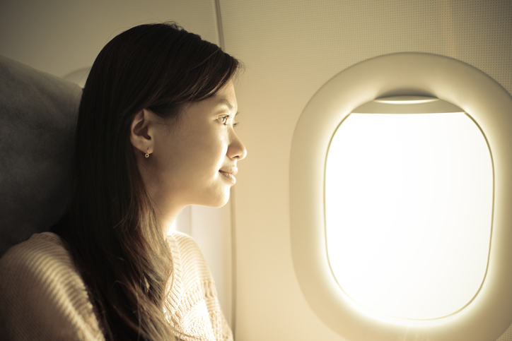 Woman sitting in airplane and looking out the window