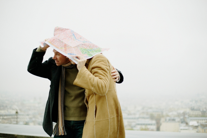 Couple taking shelter from rain under map