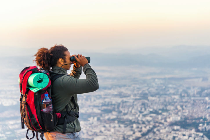 Man standing at the top of a hill and looking at view though binoculars at sunset.