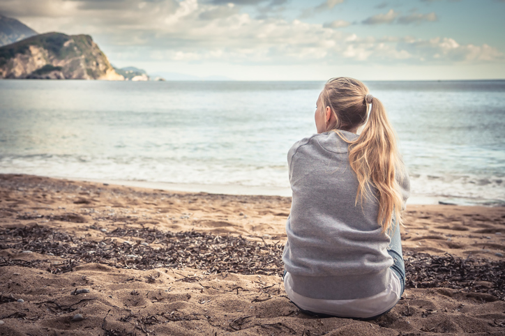 Woman in grey sweatshirt sitting at beach on cloudy day