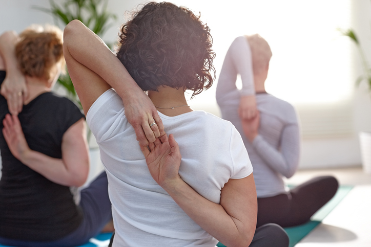 Woman stretching arms behind back in yoga class