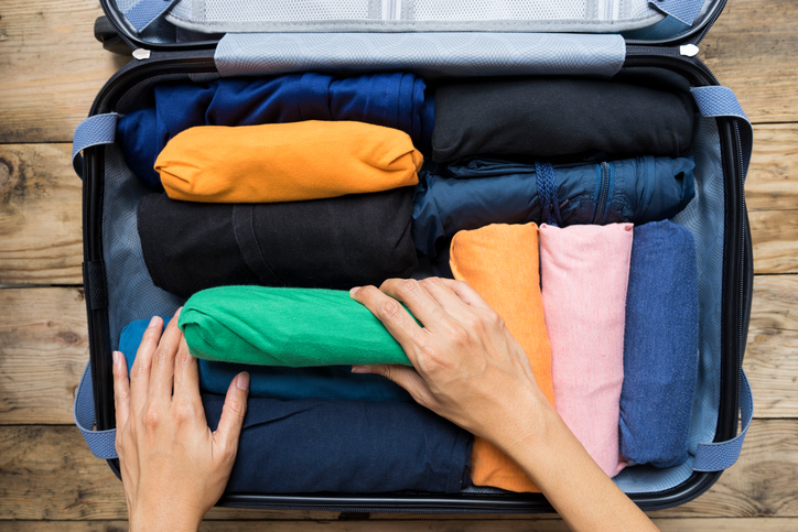 Overhead view of hands packing suitcase