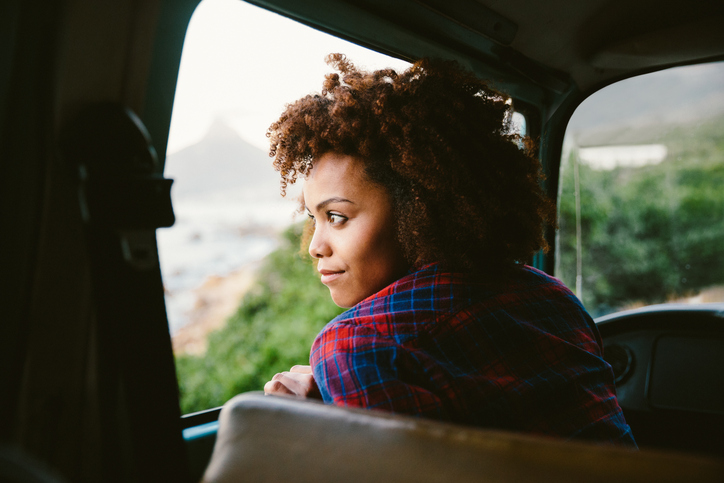 Woman thoughtfully looking out car window