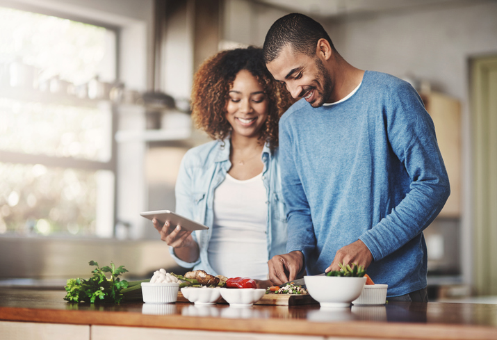 A young couple smiles as they cook together.