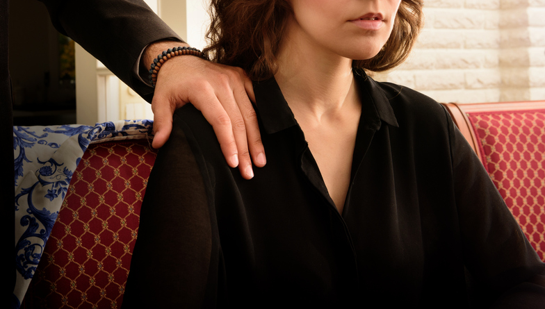 A woman frowns as a hand grabs her shoulder.
