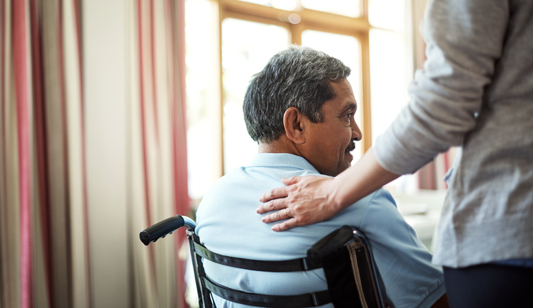 A senior man in a wheelchair glances backward when someone touches his back.