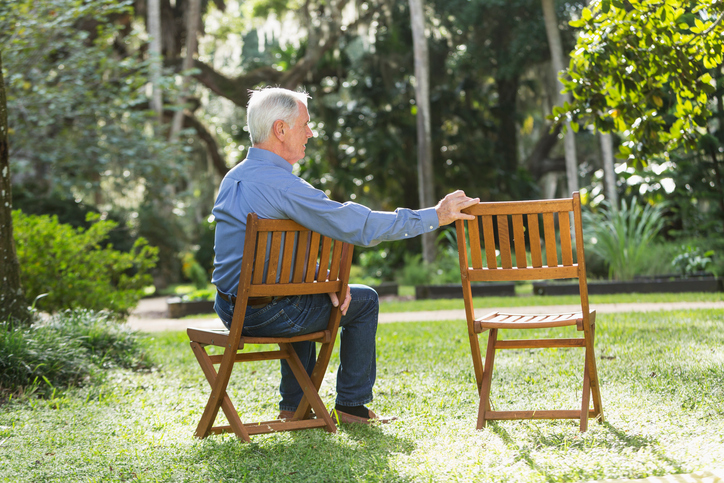 An elderly man sits outdoors next to an empty lawn chair.