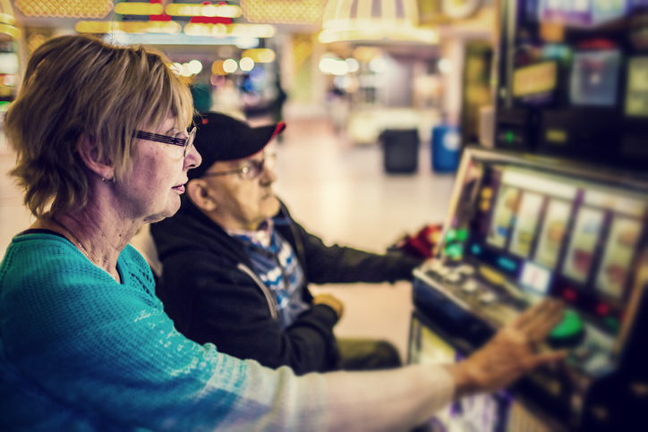 An older woman plays a slot machine while looking bored.