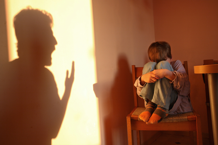 A boy cowers in a dark corner. A yelling adult casts a shadow on the wall.