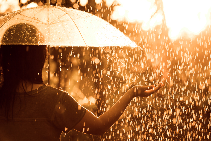 A woman holds out her hand to feel the rain coming down.