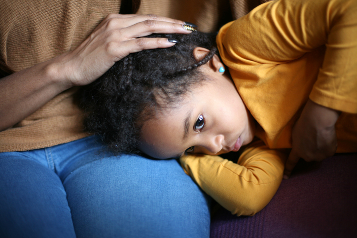 A young girl lays her head in her mother's lap. The mother rests her hand on the child's head.