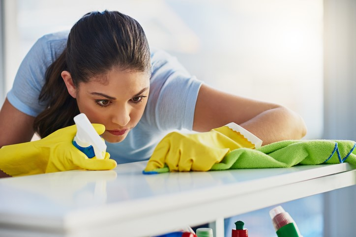 A woman in plastic gloves cleans an already spotless table.