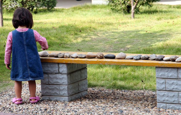 A young girl lines up all the rocks in the yard on a bench.