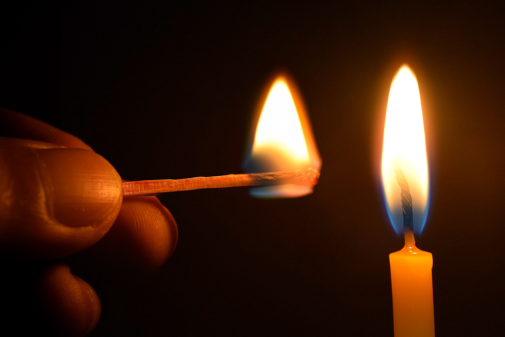A close up of fingers lighting a candle with a match.