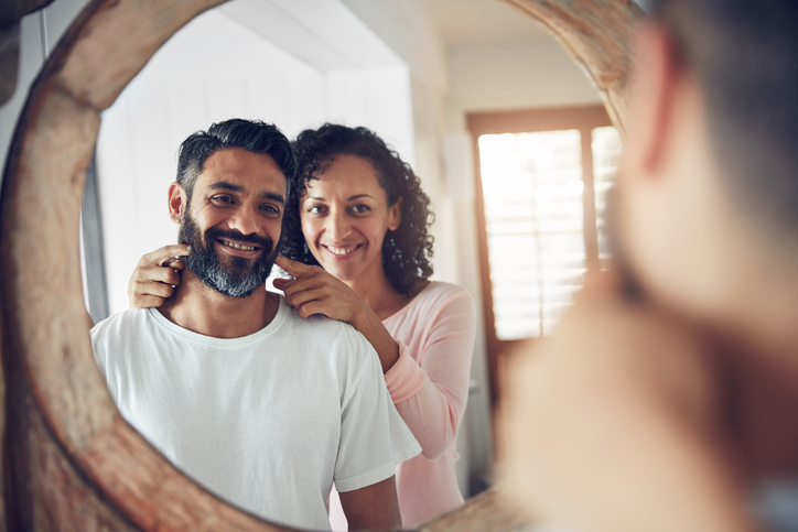 A wife encourages her husband to smile at himself in the mirror.
