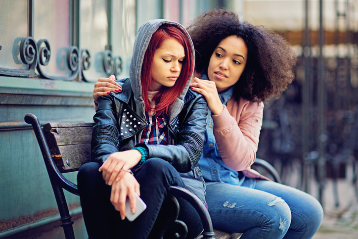 Two girls sit on a bench outside. One comforts the other after an upsetting phone call.