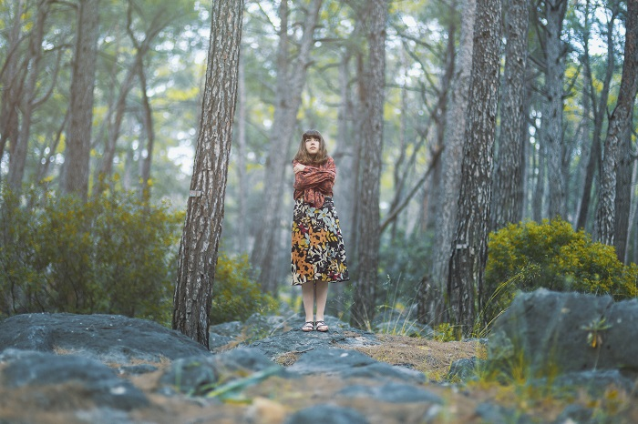 Woman stands alone in the middle of a forest.