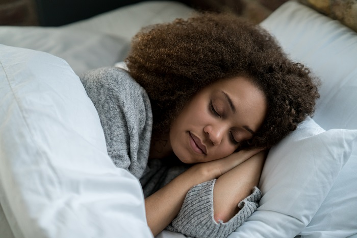 Woman sleeps peacefully with head resting on pillow.
