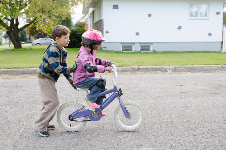 A young boy teaches his sister how to ride a bike.