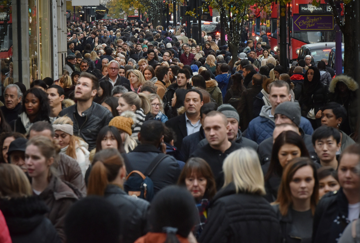 A huge crowd gathers on the street for Black Friday shopping.