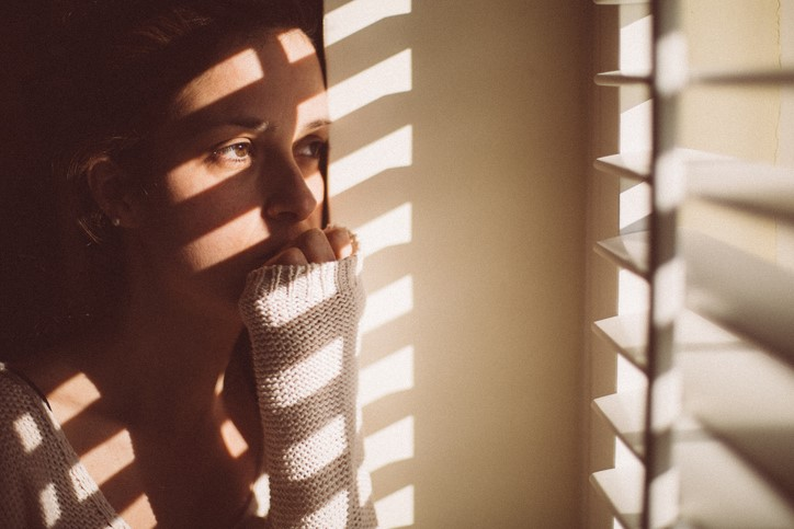 A young woman bites her nails as she stairs out her window. Sun shines in through half-open blinds.