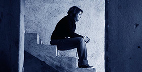A woman sits alone on secluded stairs.