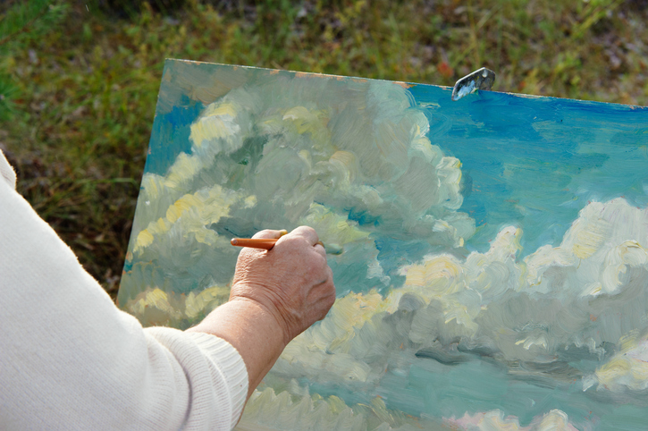A senior artist works outside, painting a blue sky and clouds.