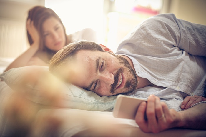 Man looks at phone in bed while his partner watches from a distance.