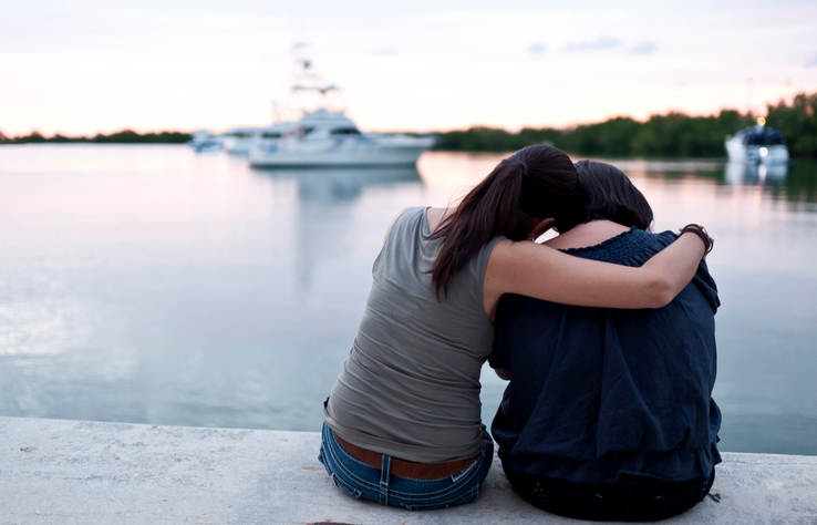 A woman hugs her friend as they watch boats in the harbor.