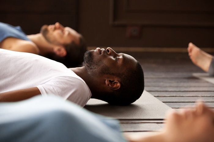 Men laying on their backs during a yoga class.