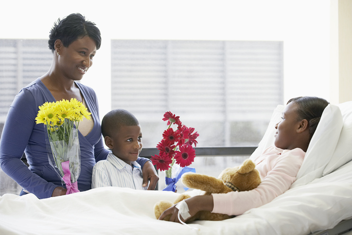 A family brings flowers to a young girl in the hospital.