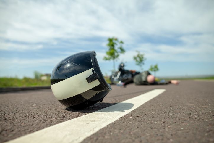 Close-up of helmet on the road, with a motorcycle and its rider lying prone in the background.