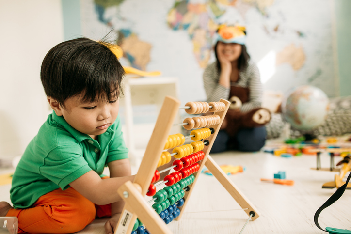 A toddler plays with an abacus while his mother watches from across the room.