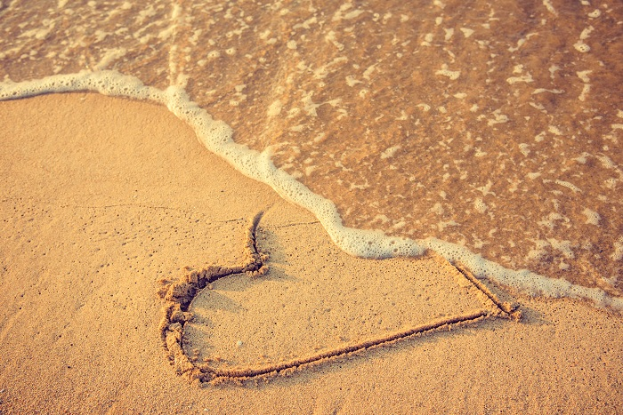 Waves washing away a heart that was drawn in the sand at the beach