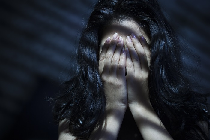 Woman hiding her face with her hands in a dark room