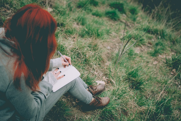 Girl with red hair sitting on some grass, writing in a journal