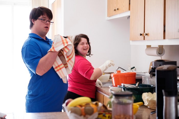 Couple with intellectual disability working together in their kitchen