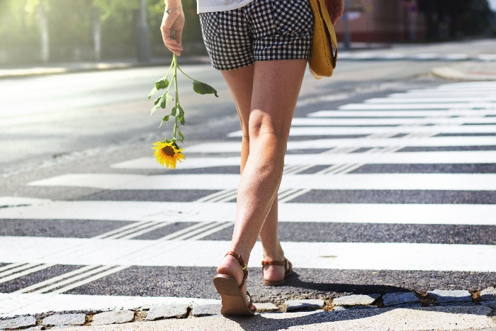 Woman crossing street holding sunflower