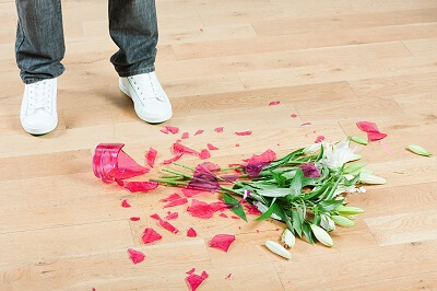 View of person's feet standing next to a broken flower vase