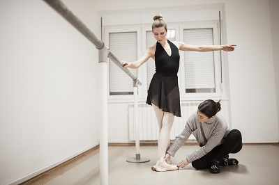 Dance instructor coaching ballerina on foot placement
